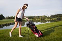 女孩有高尔夫球袋的高尔夫球运动员。 免版税库存照片