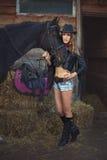 女孩有他的马槽枥的牛仔 库存照片