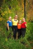 女孩朋友在森林里在秋天 免版税库存照片