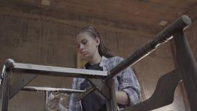 女孩木匠,设计师,装饰员,在关于老家具的恢复的一个车间工作 股票视频
