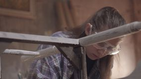 女孩木匠,设计师,装饰员,在关于老家具的恢复的一个车间工作 影视素材