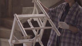 女孩木匠,设计师,装饰员,在关于老家具的恢复的一个车间工作 股票录像