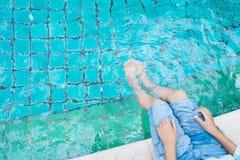 女孩松弛脚用在水池的水 免版税库存图片
