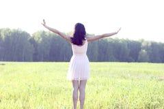 女孩桃红色礼服跳跃草甸夏天,乐趣,放松形象太阳喜悦的幸福概念想法 免版税库存照片
