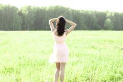 女孩桃红色礼服跳跃草甸夏天,乐趣,放松形象太阳喜悦的幸福概念想法 免版税图库摄影