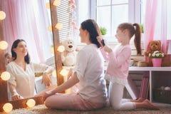 女孩梳她的母亲` s头发 免版税库存照片