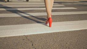 女孩横渡步行交叉点 有红色鞋子的腿在高跟鞋特写镜头 影视素材