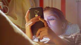 女孩正面图有智能手机冲浪的互联网的在睡觉前 股票视频