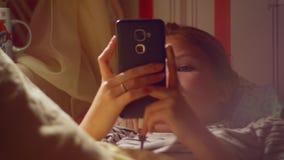 女孩正面图有智能手机冲浪的互联网的在睡觉前 股票录像