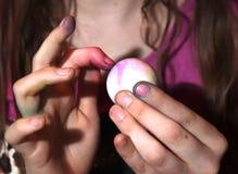 女孩死的复活节彩蛋和她的手指 免版税图库摄影