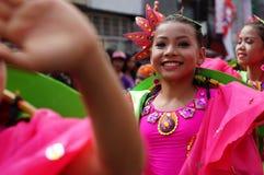 女孩民族服装的狂欢节舞蹈家在沿路的欢欣跳舞 免版税库存图片