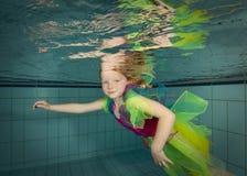 女孩水下一点的游泳 免版税库存照片