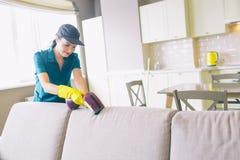 女孩沙发清洁边缘的图片  她使用小吸尘器 妇女是专业 她完全工作 库存图片