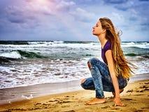 女孩沙子海滩的周道地调查距离到日落前光芒  免版税库存照片