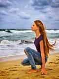 女孩沙子海滩的周道地调查距离到日落前光芒  库存照片