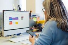 女孩治疗师在一个电话期间的一个办公室,使用预定网上的日历患者任命 日历计划者 库存照片
