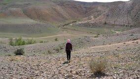 女孩沿一个离开的石地形在小山和山背景中走  股票录像