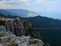 女孩沿在一个悬崖的一座吊桥走Ai陪替氏山的 在山的极端 免版税库存照片