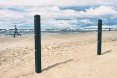 女孩沿在波罗的海的海滩跑 免版税库存照片