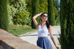 女孩沿在领域中的路走 库存照片
