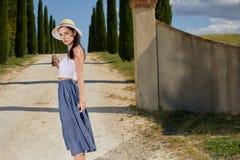女孩沿在领域中的路走 免版税库存照片