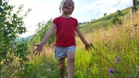 女孩沿在高草和野花中的道路跑 影视素材