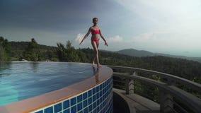 女孩沿水池的边在山股票英尺长度录影上面的走 股票视频