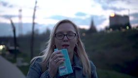 女孩沿河的平衡的堤防走并且通过管喝从箱子的汁液 股票视频