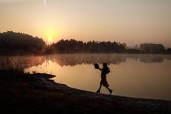 女孩沿海滩跑早晨的早晨日出 雾 女孩剪影 库存照片