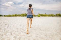女孩沿海滩跑 免版税库存照片