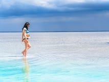 女孩沿盐湖的表面走在温泉渡假胜地 海滩的少妇与白色沙子和美丽 免版税库存照片