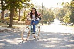 女孩沿街道的骑马自行车对学校 库存照片