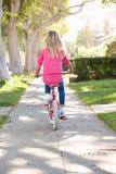 女孩沿道路的骑马自行车 免版税库存照片