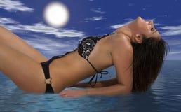 女孩泳装放松的说谎在海,朝向掀动  覆盖天空 免版税库存图片