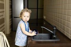 女孩洗碗在厨房里在家 免版税图库摄影