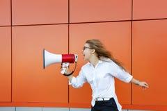 女孩活动家叫喊对扩音器 库存照片