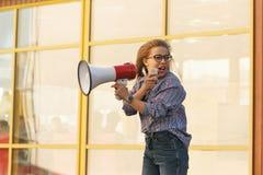 女孩活动家在扩音器呼喊 免版税图库摄影