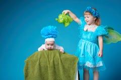 女孩浇灌她的弟弟 库存照片