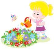 女孩浇灌的花 免版税库存图片