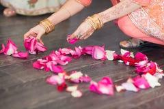 女孩消散玫瑰在地板上的花瓣 图库摄影