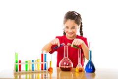 女孩混合在烧瓶的化学制品 免版税库存照片
