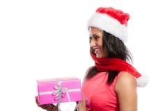 女孩混合的族种有礼物盒的圣诞老人帽子 图库摄影