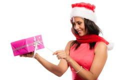 女孩混合的族种有礼物盒的圣诞老人帽子 免版税库存图片