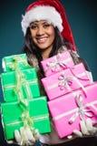 女孩混合的族种有礼物盒的圣诞老人帽子 免版税库存照片