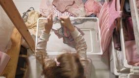 女孩清扫在家庭衣橱的衣裳 股票录像