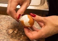 女孩清除从壳的鸡蛋 图库摄影