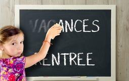 女孩清除在黑板的假期 免版税图库摄影