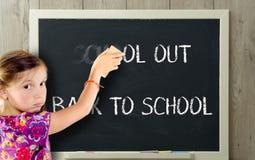 女孩清除学校黑板的 库存照片