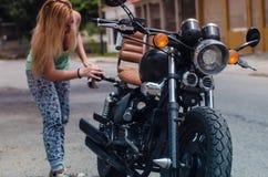 女孩清洁摩托车 免版税图库摄影