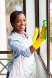女孩清洁玻璃窗 免版税库存照片
